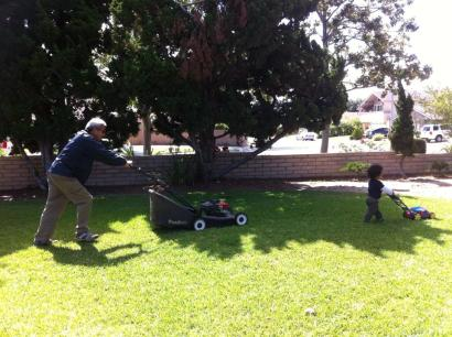 My dad mowing the lawn and my son wanting to copy him.